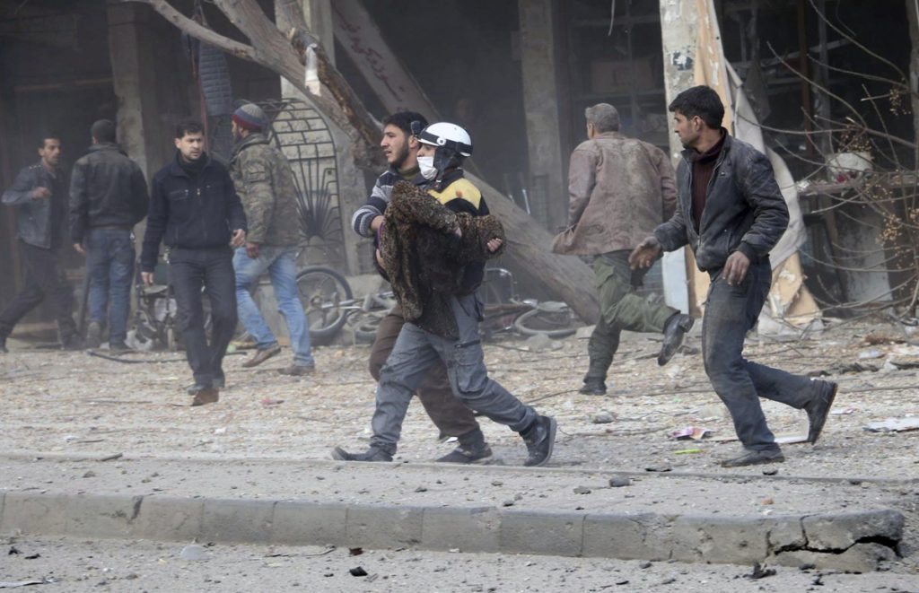 This photo provided by the Syrian Civil Defense White Helmets, which has been authenticated based on its contents and other AP reporting, shows a civil defense worker carrying a victim after airstrikes hit a rebel-held suburb near Damascus on Thursday.