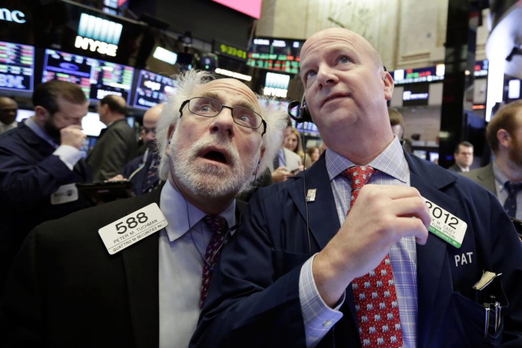 Traders Peter Tuchman, left, and Patrick Casey work on the floor of the New York Stock Exchang on Thursday.