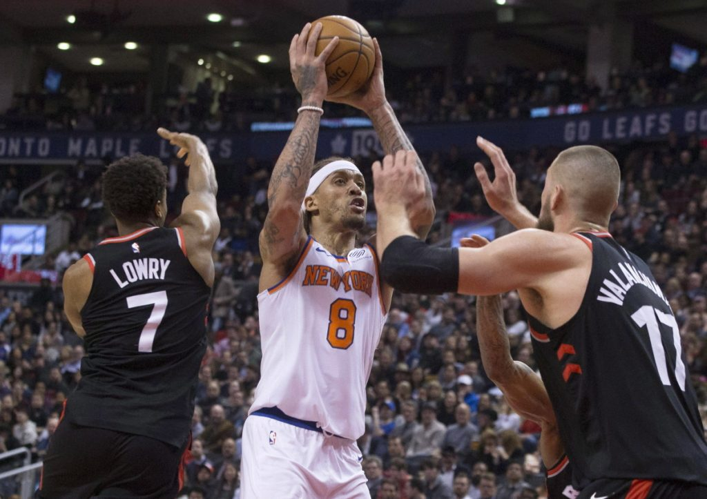 New York's Michael Beasley shoots between Toronto's Kyle Lowry and Jonas Valanciunas, right, in the second half Thursday night in Toronto.