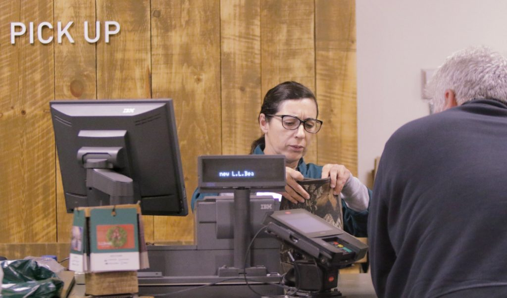 Maria Higgins helps a customer returning boots at the customer service area at L.L. Bean in Freeport in 2016.