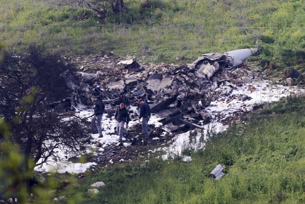 """Israeli security personnel stand around the wreckage of an F-16 that crashed in northern Israel on Saturday. The Israeli military shot down an Iranian drone it said infiltrated the country early Saturday before launching a """"large-scale attack"""" on at least a dozen Iranian and Syrian targets inside Syria, in its most significant engagement since the fighting in Syria began in 2011. Responding anti-aircraft fire led to the downing of the Israeli fighter plane."""