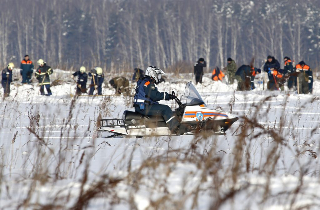 Russian Emergency Situations Ministry employees and Russian police officers work at the scene of a AN-148 plane crash in Stepanovskoye village, about 25 miles from the Domodedovo airport in Russia on Monday. A Russian passenger plane carrying 71 people crashed Sunday near Moscow, killing everyone aboard shortly after the jet took off from one of the city's airports.