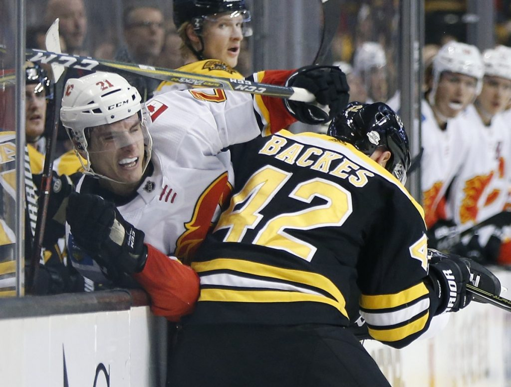 Boston's David Backes checks Calgary's Garnet Hathaway in the first period Tuesday night in Boston. Backes had two assists as the Bruins topped the Flames 5-2 in their last home game until Feb. 27.