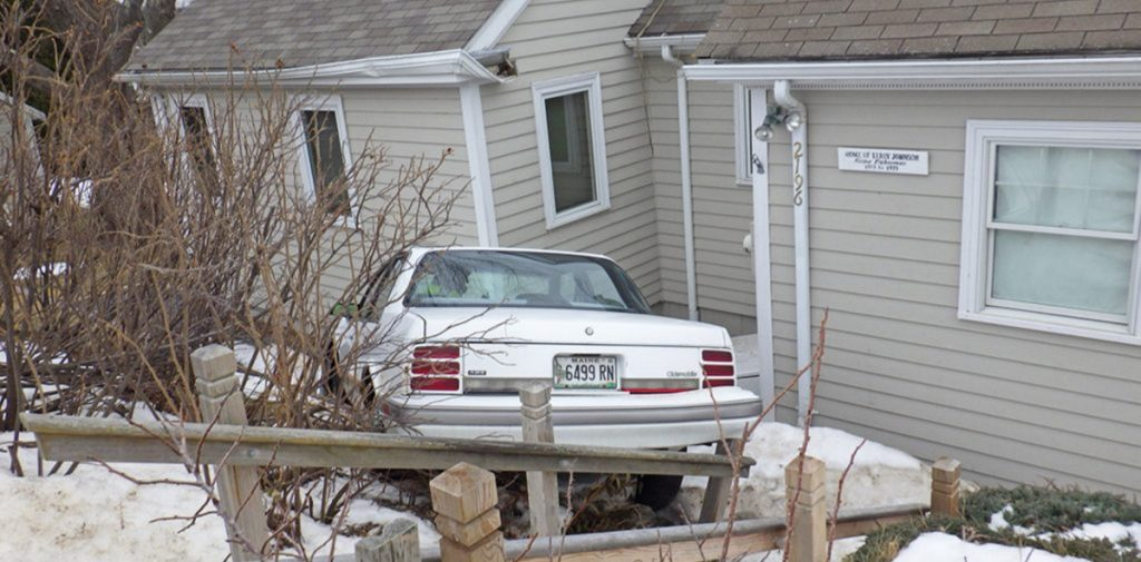 After going airborne and slamming into the home's roof, the car came to rest against the structure's exterior wall.