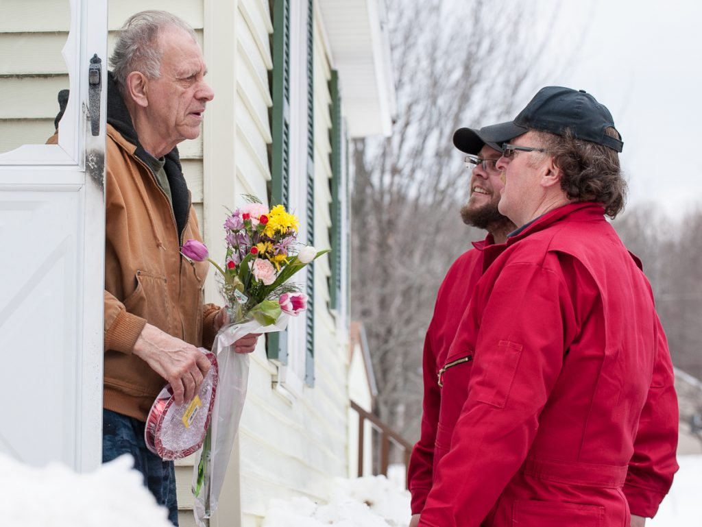 Gilman Dube, flowers and chocolates in hand, stands in the doorway of his Auburn home and learns he is the recipient of free heating oil for Valentine's Day.