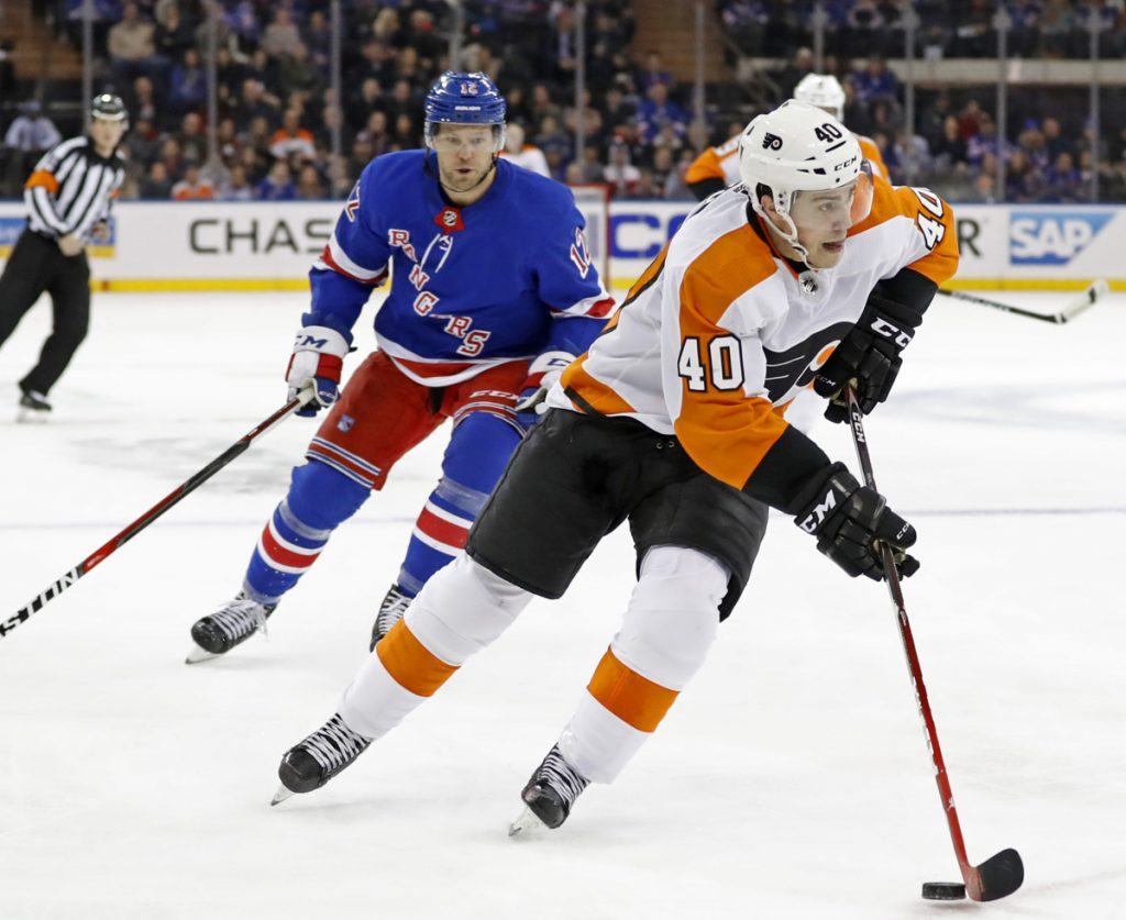 Flyers center Jordan Weal carries the puck with Peter Holland of the Rangers in pursuit during Philadelphia's 7-4 victory Sunday in New York.