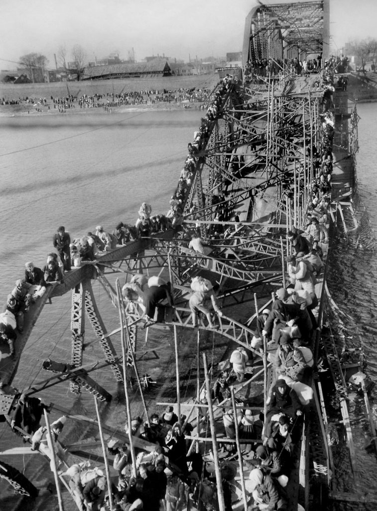 Fleeing refugees crawl perilously over the shattered girders of a bombed bridge in Pyongyang, North Korea, in a photo taken by Max Desfor. The renowned photographer died this week at age 104.