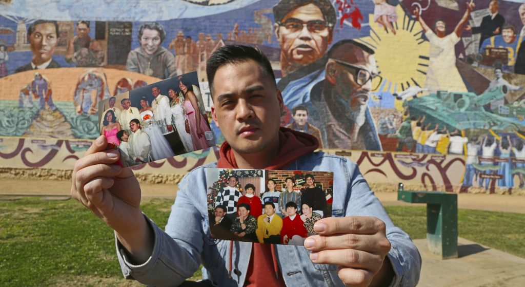 Filipino American Jeff DeGuia holds up family pictures at Unidad Park in Los Angeles earlier this month. DeGuia, 28, says it took his mother more than a decade to bring two sisters from the Philippines.