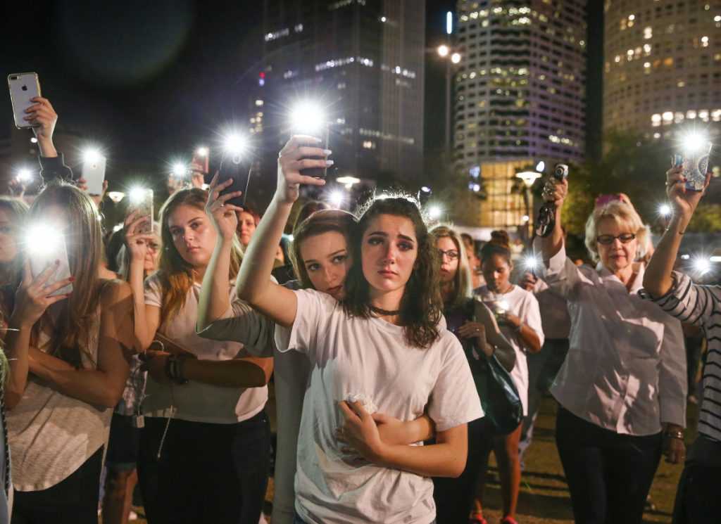 Mary Claire Foley, center left, 16, embraces Ariana Skafidas, 16, students at Henry B. Plant High School at Curtis Hixon Park in downtown Tampa, Fla., on Monday as they raise their lights during a vigil to honor victims of last week's shooting at Marjory Stoneman Douglas High School in Parkland, Fla.