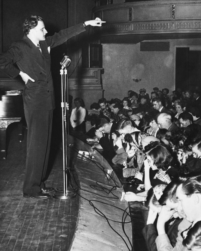 "Billy Graham gestures as several hundred people answer the call to have their souls ""cleansed of sin"" at a rally in City Hall Auditorium in Portland on March 28, 1950, as he launched his New England tour."