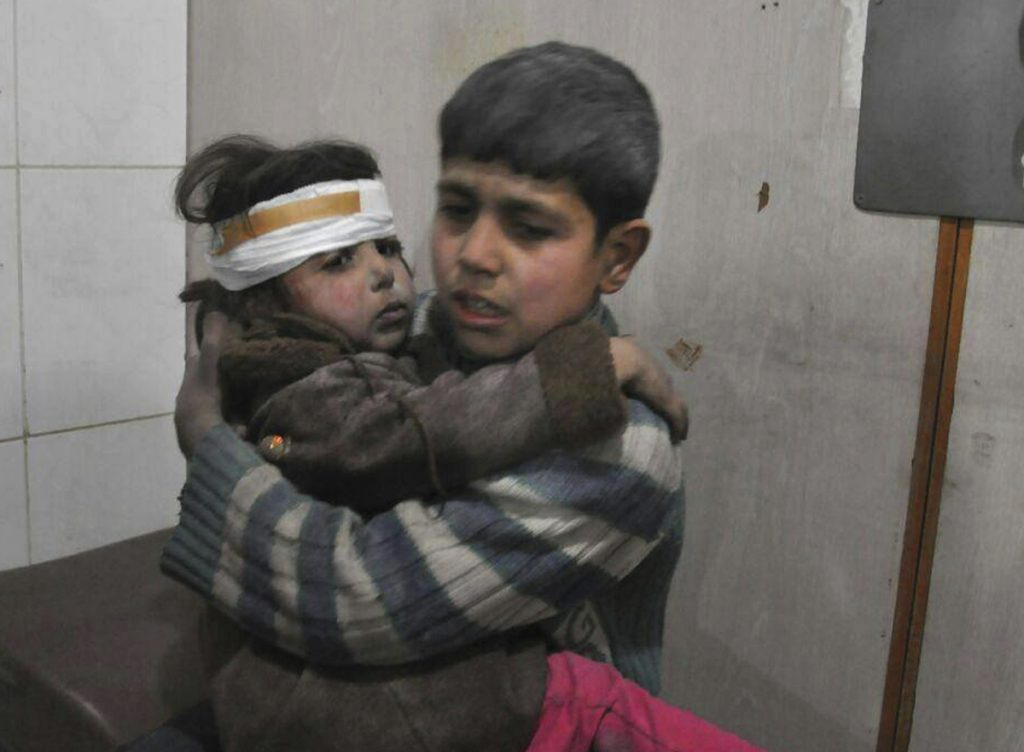 Two Syrian children who were wounded during airstrikes sit in a makeshift hospital in Ghouta on Feb. 21.