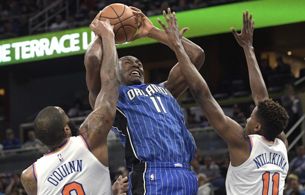 Bismack Biyombo of the Orlando Magic has his shot blocked by Kyle O'Quinn of the New York Knicks as Frank Ntilikina helps defend during the first half of the Knicks' 120-113 victory Thursday night.