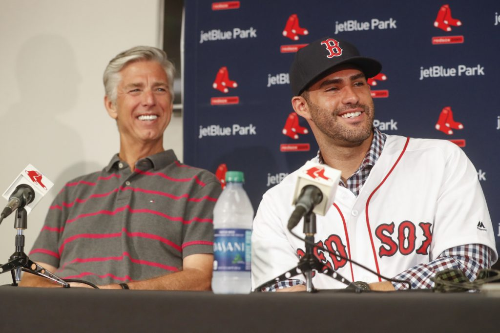 Boston Red Sox baseball player J.D. Martinez, right, smiles alongside David Dombrowski, president of baseball operations, during a news conference announcing his signing with the team, Monday, Feb. 26, 2018, in Fort Myers, Fla. (AP Photo/John Minchillo)