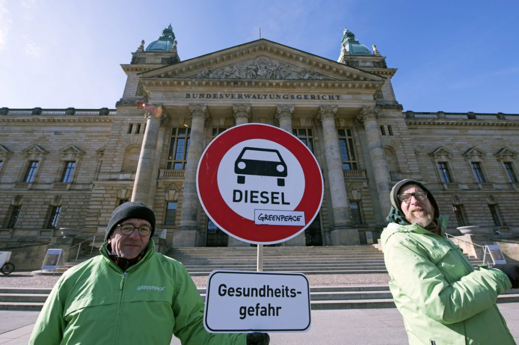 Environment activists stand in front of the Federal Administrative Court prior to a trial in Leipzig, Germany, Tuesday. The German court ruled Tuesday that cities can impose driving bans on diesel cars to combat air pollution, a decision that could affect millions of drivers and the country's powerful auto industry.