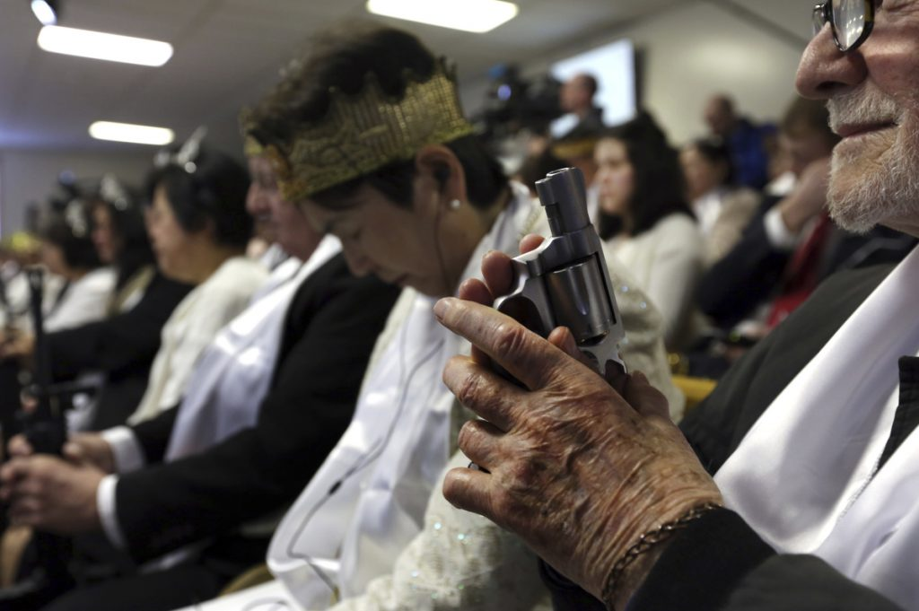 A man holds an unloaded weapon on Wednesday at the World Peace and Unification Sanctuary in Newfoundland, Pa.