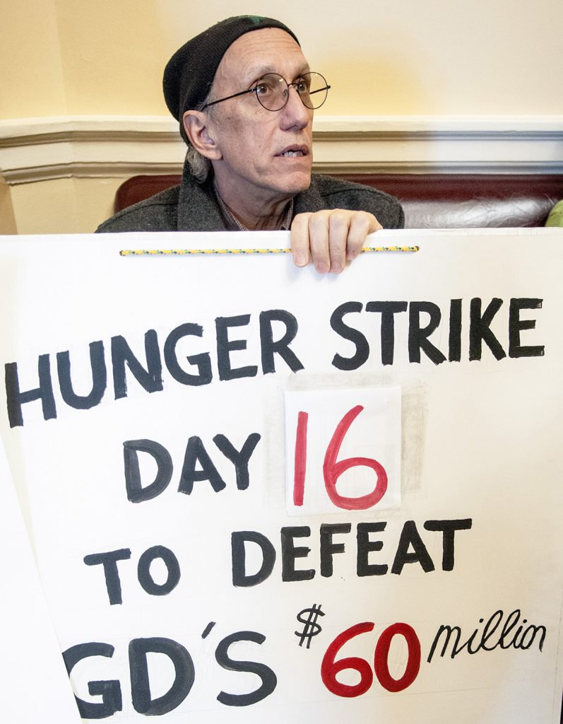 Bruce Gagnon, of Bath, holds his sign opposing Bath Iron Works' tax credits last month at the State House. Gagnon was on the 16th day of a hunger strike.