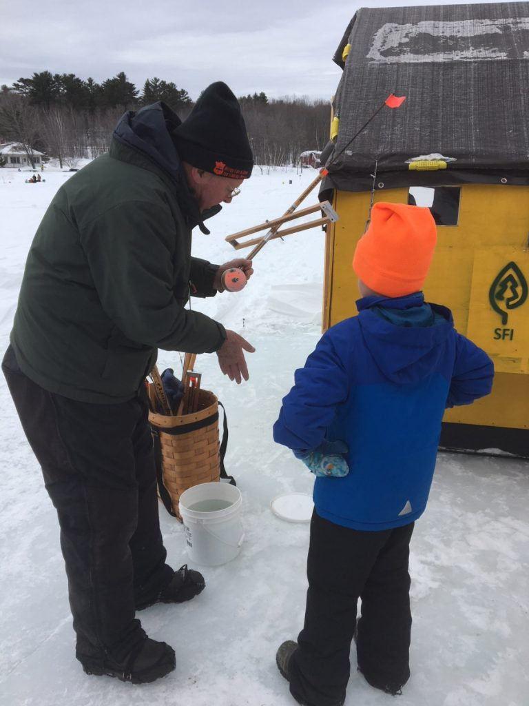 Alan Hart, a member of the Wilton Fish and Game Association, shows a youngster an ice fishing trap during last year's ice fishing clinic. A free ice fishing clinic for all ages will be held from 10 a.m. to 2 p.m. Feb. 17, as part of the ice fishing derby at Wilson Lake.