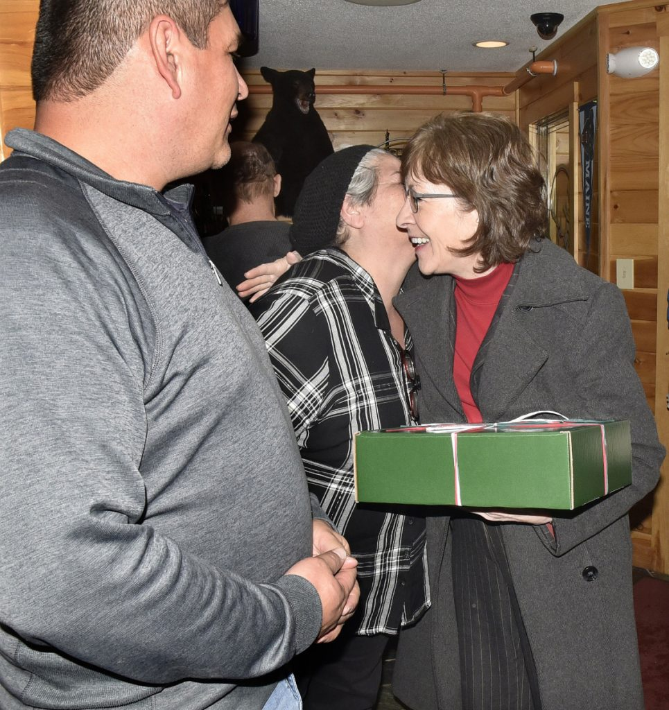 U.S. Sen. Susan Collins, right, hugs Marie Harnois, of Passamaquoddy Maple, after she gave the senator a box of maple syrup Thursday when Collins stopped at Schmoose's Bar and Grill in Jackman. Joseph Socobasin is at left. Collins came to show her support for the Jackman residents, whose town received negative publicity after the former town manager publicly expressed his racist views.