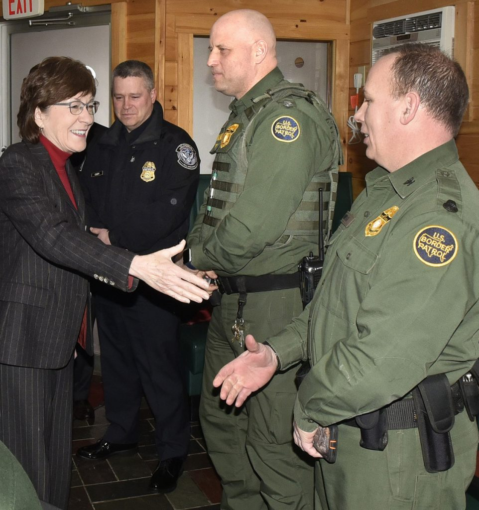 U.S. Sen. Susan Collins shakes hands Thursday with Mike Smith, right, a U.S. Border Patrol officer, after stopping at Schmoose's Bar and Grill in Jackman. Ed Cuddy, left, of Customs Border Protection and officer Dennis Harmon also greeted the senator. Collins came to show her support for the residents whose town received negative publicity after the former town manager publicly expressed his racist views.