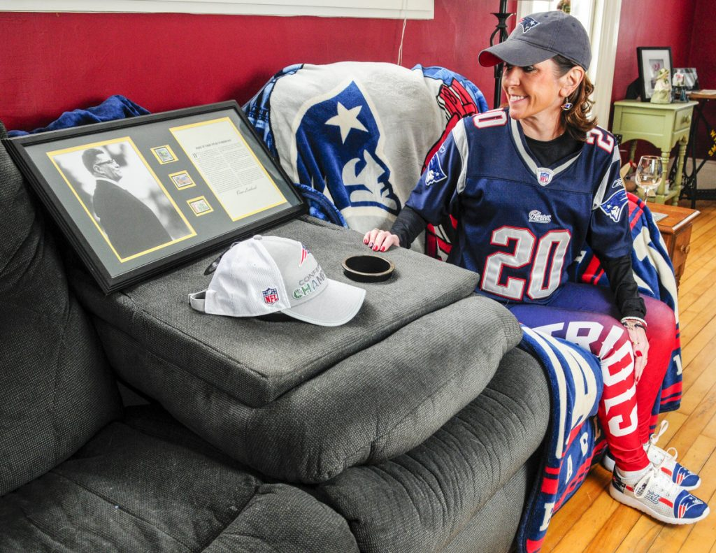 8d43f022e Patriots fan Michele Malinowski poses for a photo in her game time spot on  Thursday in her family s Pittston home. Beside her is a framed copy of  Vince ...