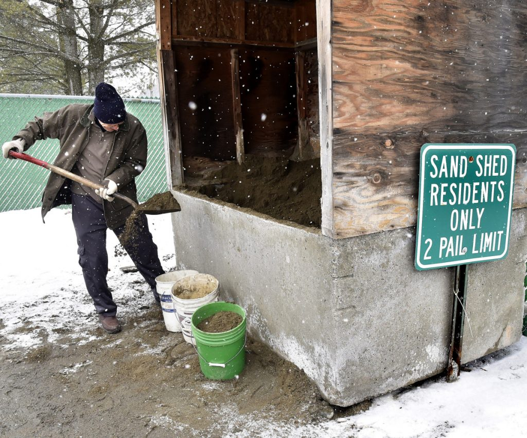 As snow falls Tuesday, Norton Webber fills buckets with sand at the Waterville Public Works department to stem icy conditions as a steady stream of residents prepared for Wednesday's snowstorm.
