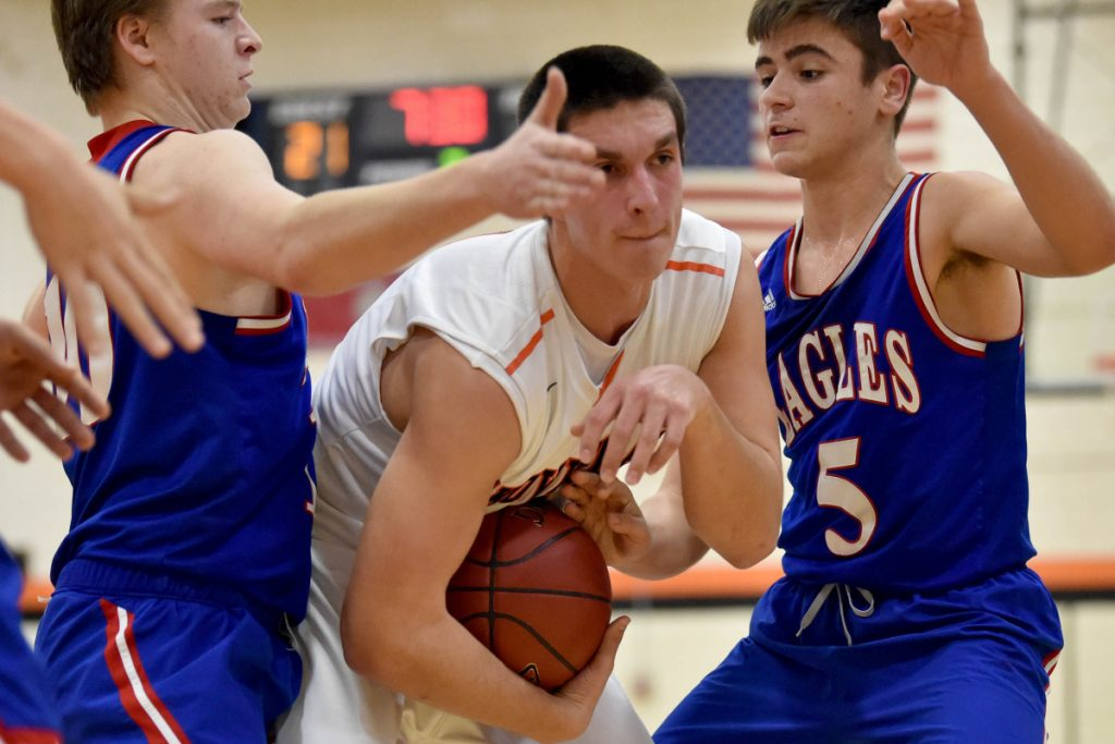 Skowhegan's Marcus Christopher, center, battles for a rebound with Messalonskee's Colby Charette, left, and Chase Warren during a Kennebec Valley Athletic Conference Class A game Tuesday in Skowhegan.
