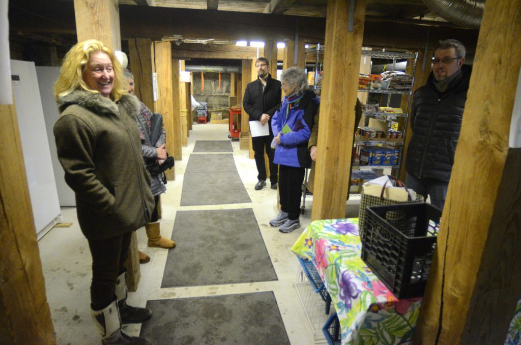 Director Jeanne Langsdorf, left, leads a tour of the Hallowell Food Bank on Thursday in the fire house basement in Hallowell.