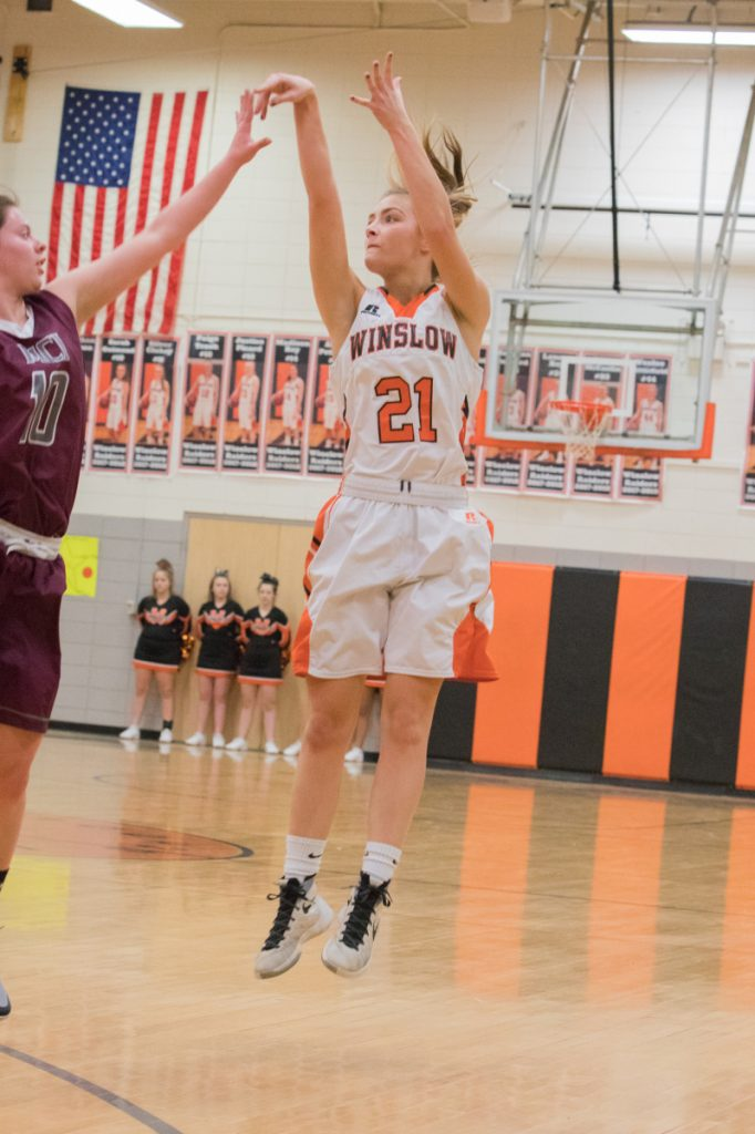 Photo by Jennifer Bechard   Winslow's Haley Ward launches a 3-pointer while MCI's Sydney Farrar defends during a Class B North game Thursday night in Winslow.