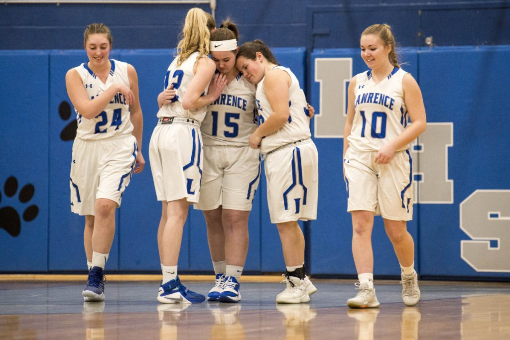Lawrence's Hunter Mercier (15) is comforted by teammates Kirsten Gordon (12) and Haley Holt, right center, after scoring the first two points of the game and exiting with an injury against Skowhegan on Thursday in Fairfield.