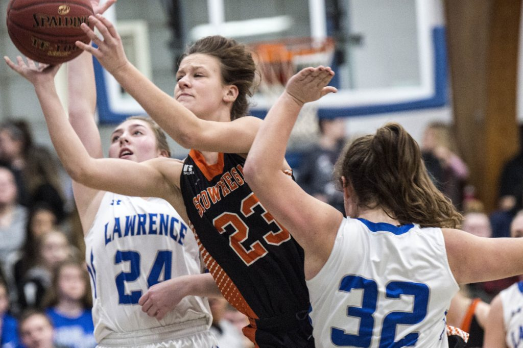 Skowhegan's Alyssa Everett (23) drives to the basket as she is defended by Lawrence's Haley Holt (32) and Molly Folsom (24) in a Class A North game Thursday in Fairfield.