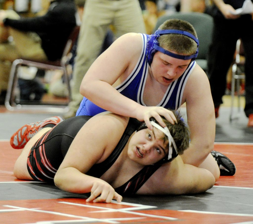 Erskine's Jake Peavey pushes down on Wells' Matt Healy during their match in the 285-pound weight class last season in Wells.