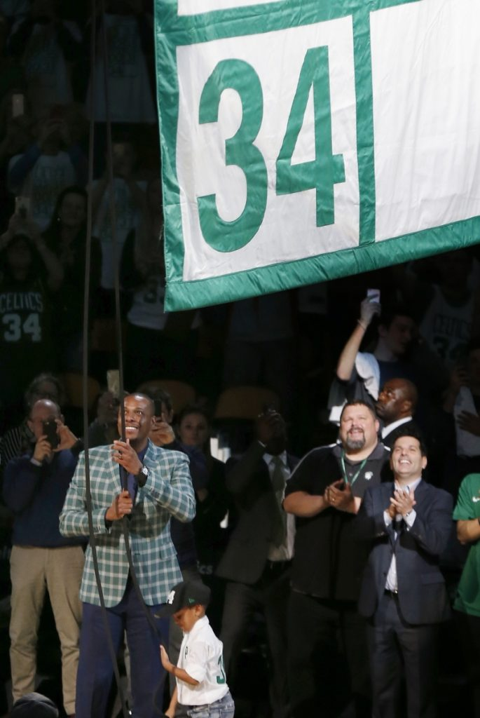 Former Boston Celtics star Paul Pierce, left, raises a banner during a ceremony to retire his number following a game against the Cleveland Cavaliers on Sunday in Boston.