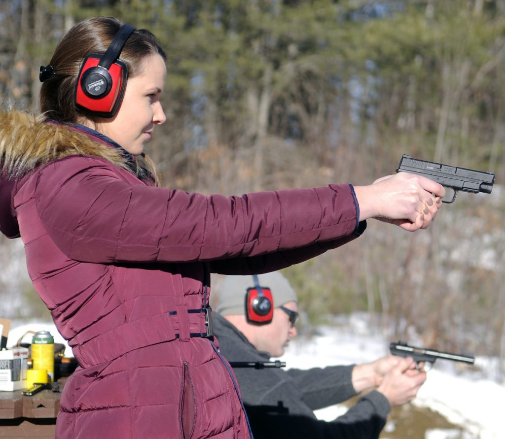 Katherine Pollock fires a pistol with Rob Sibley on Jan. 6, 2016, at the Department of Inland Fisheries & Wildlife range in Augusta.