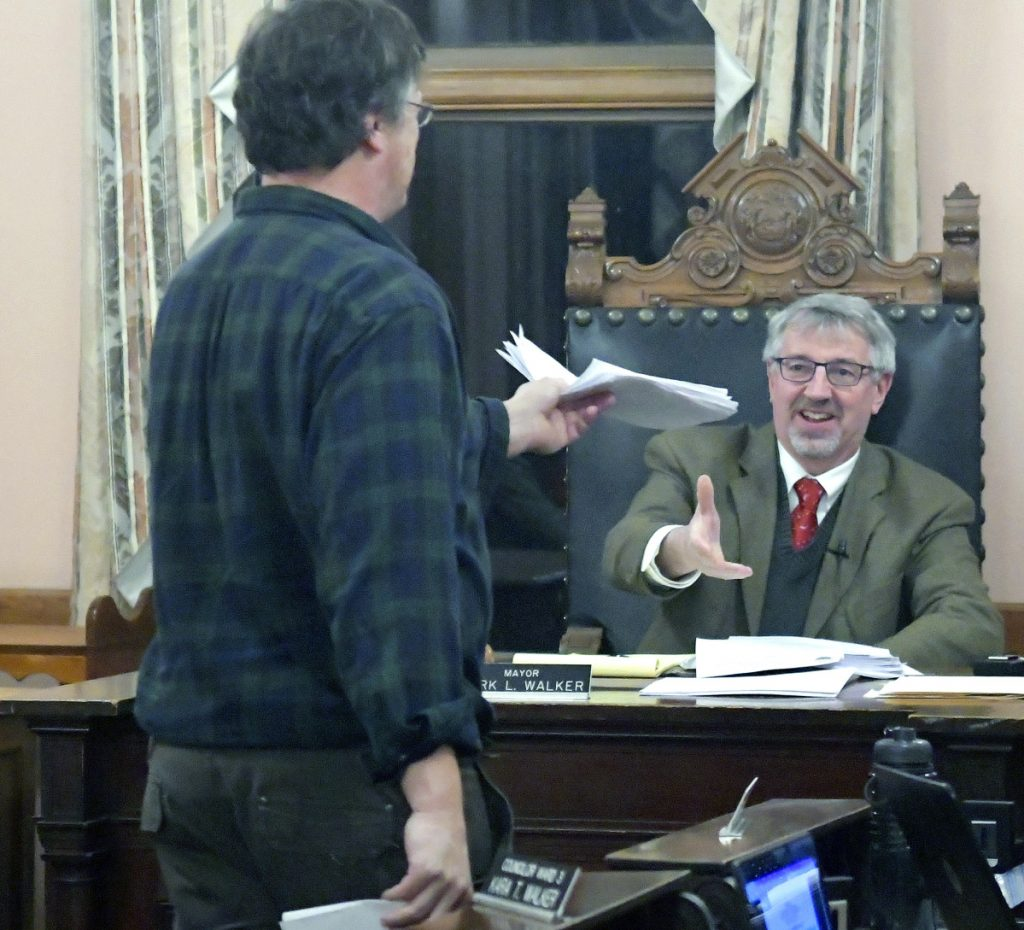 Geoff Houghton hands a petition to Hallowell Mayor Mark Walker on Monday urging the installation of a crosswalk in front of his Water Street business, The Liberal Cup, during a Hallowell City Council meeting. The council voted in favor of adding the feature to the U.S. Route 201 reconstruction project, which has been in planning for several years.