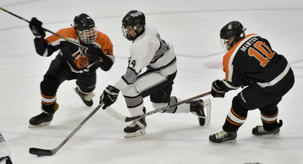 Staff photo by David Leaming   Kennebec's Hunter Brown, middle, skates between Gardiner defenders, including Conner Manter at right, during a game Monday at Colby College.
