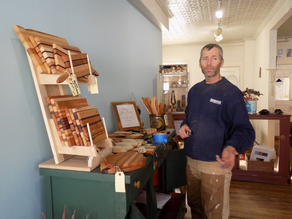 Vera's Iron and Vine on Front Street in Farmington now carries the work of several local artisans. John Nichols sets up a display of his wooden pieces.