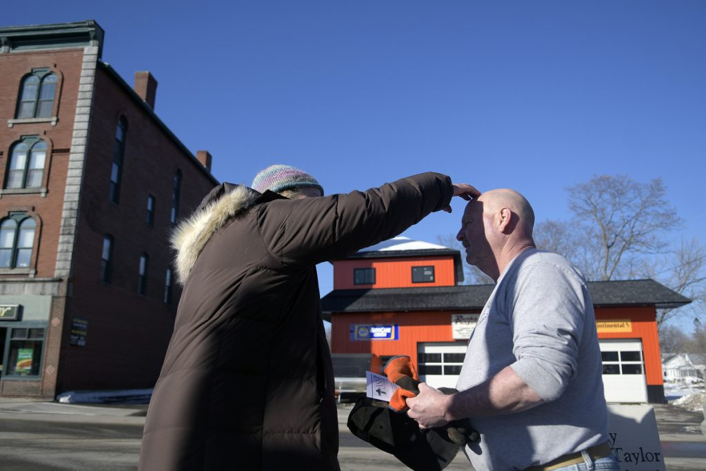 Rev. Susan Taylor, of St. Andrew's Episcopal Church, places ashes on the head of Steve Kennedy in downtown Winthrop on Wednesday.
