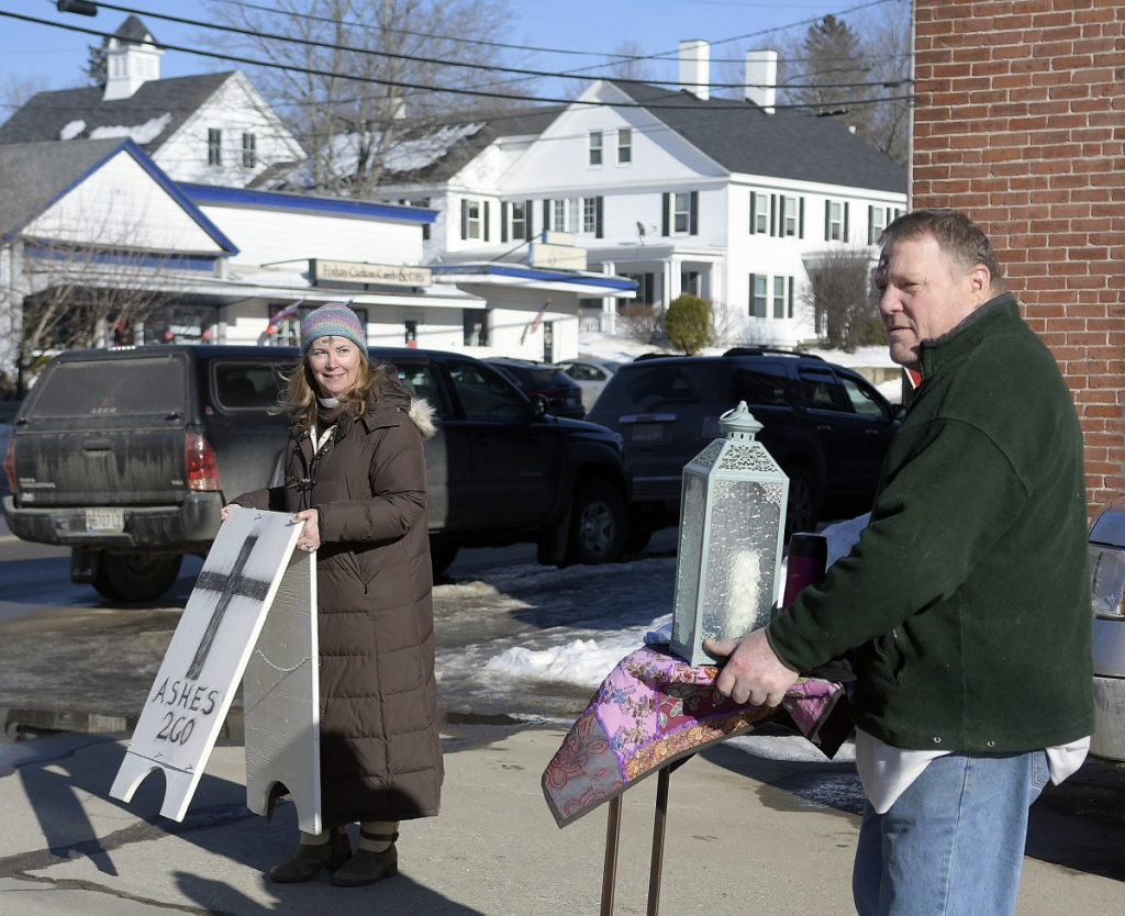 Rev. Susan Taylor, of St. Andrew's Episcopal Church, and parishioner Bob Somes set up a spot in downtown Winthrop on Wednesday to place the sign of the cross on people with ashes.