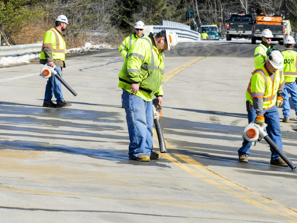 Department of Transportation workers blow-dry the road as they prepare to paint striping on Wednesday at the new bridge at Exit 109 over Interstate 95 in Augusta. The bridge was damaged by an unidentified vehicle or piece of equipment last year.