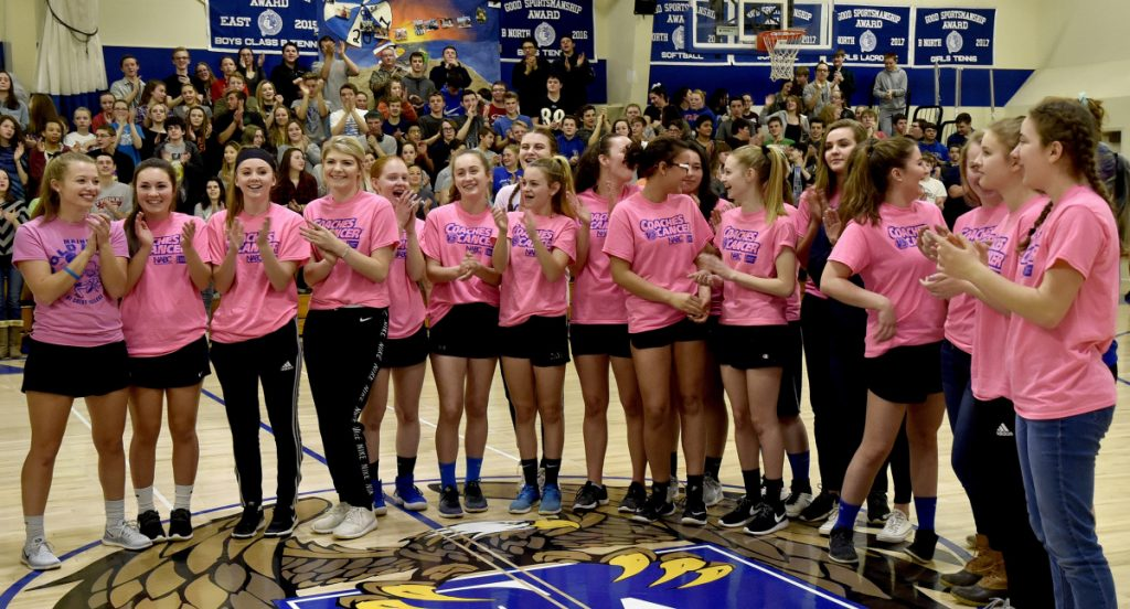 Students and staff at Erskine Academy applaud the girls basketball team, which was recognized for raising $10,000 for the American Cancer Society during a ceremony Tuesday at the South China school.