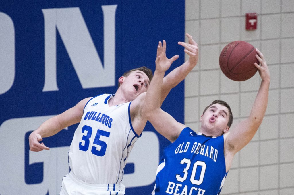 Madison's Max Shibley (35) battles for the rebound with Old Orchard Beach's Kyle Allen (30) in a Class C South preliminary game Wednesday in Madison.