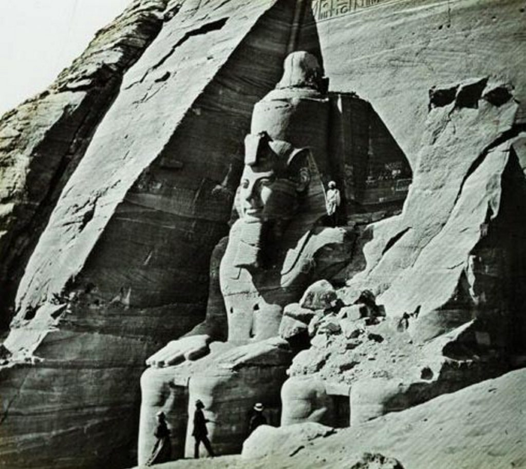 The Temple of Abu Simbel at the southern border of Egypt, built by pharaoh Ramesses II about 1250 B.C. This image is a stereoview photograph on glass taken about 1865 and shows some early tourists at the base of the 65-foot colossi of the king.