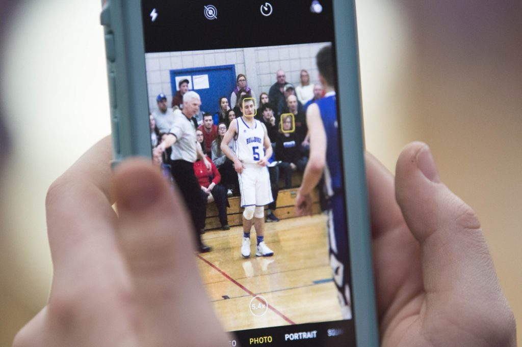 A Madison Area Memorial High School students snaps a photo Tuesday of Sean Whalen (5) in the Class C boys preliminary game against Old Orchard Beach High School in Madison.