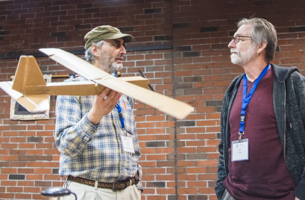 Jon Silverman, left, of Augusta, a recently certified FAA drone pilot, holds a drone made of cardboard Saturday while speaking to Ed Campbell, a land surveyor from Londonderry, N.H. The two were attending a conference at University of Maine at Augusta on using drones for business purposes.