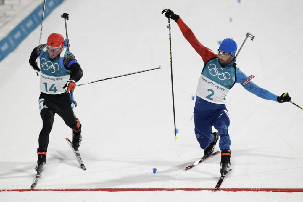 Simon Schempp, of Germany, left, and Martin Fourcade, of France, right, race across the finish line during the men's 15-kilometer mass start biathlon Sunday at the 2018 Winter Olympics in Pyeongchang, South Korea.