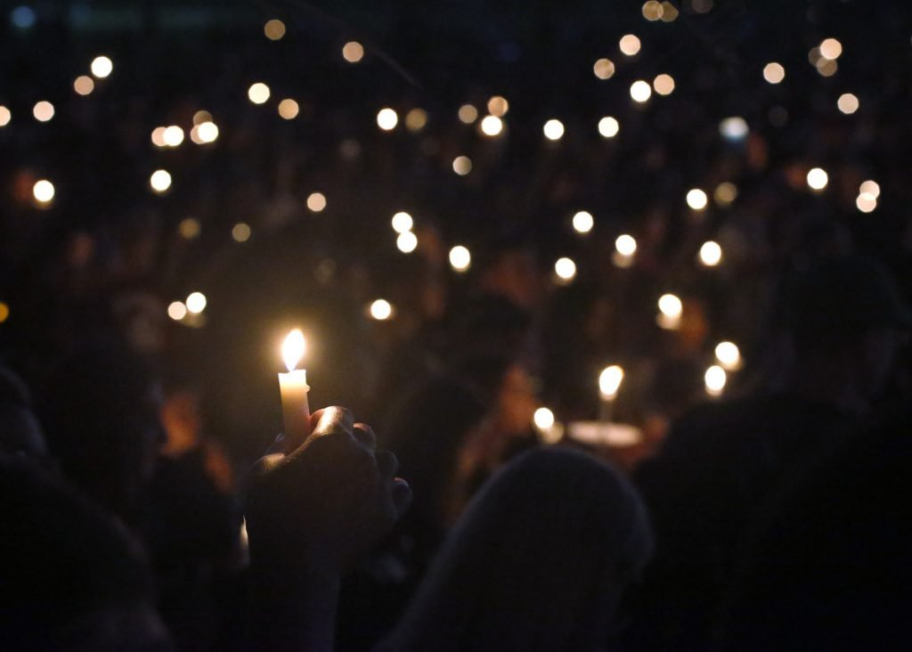 Attendees hold up their candles at a candlelight vigil for the victims of the shooting at Marjory Stoneman Douglas High School in Parkland, Florida.