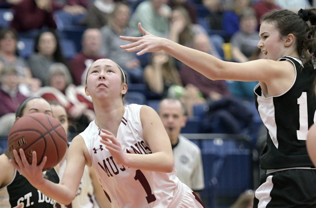 Staff photo by Andy Molloy   Monmouth guard Tia Day shoots as St. Dominic's Madison Leslie defends during a Class C South quarterfinal game Tuesday afternoon at the Augusta Civic Center.