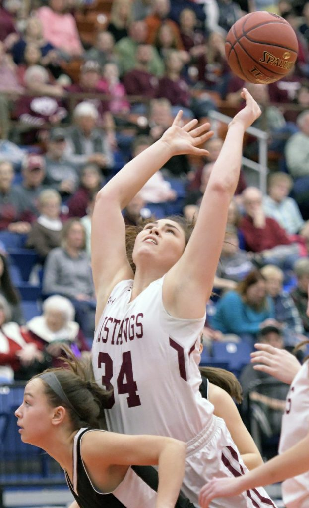 Monmouth's Destiny Clough reaches for the ball on the back of St. Dominic's Rileigh Stebbins during a Class C South quarterfinal game Tuesday at the Augusta Civic Center.