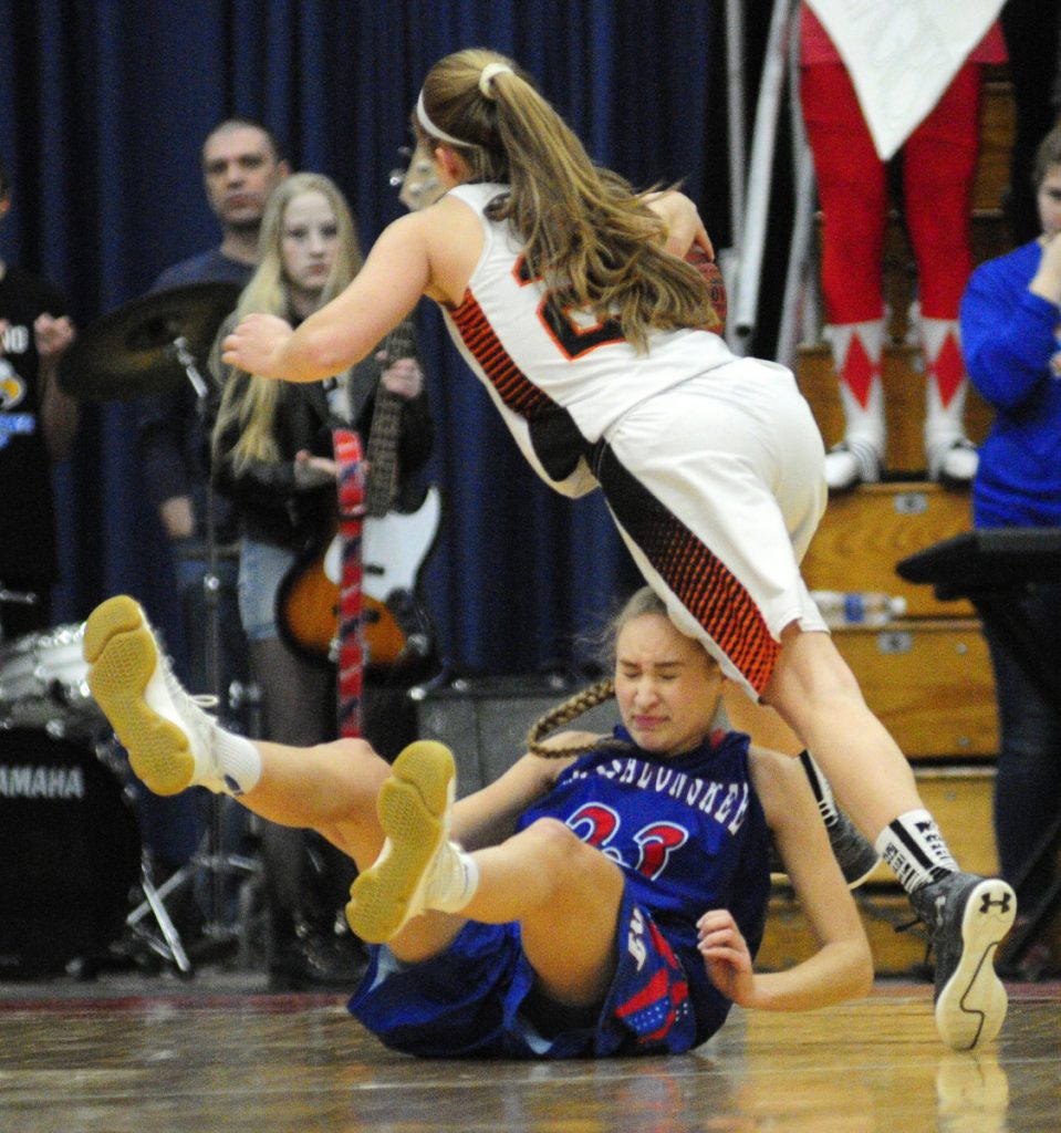 Skowhegan junior guard Sydney Ames, top, runs over Messalonskee senior guard/forward Ally Turner during a Class A North semifinal game Wednesday at the Augusta Civic Center.