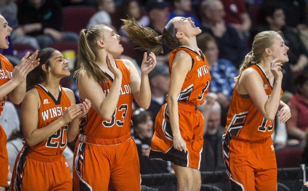 The Winslow High School girls basketball bench celebrates a 3-pointer against John Bapst during a Class B North semifinal game Wednesday at the Cross Insurance Center in Bangor.